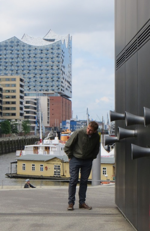 The black building on the right houses a model of the new Elbphilharmonie, an amazingly technically advanced concert hall that is visible in the background.  Recordings are played through the ear trumpets on the wall of the model.